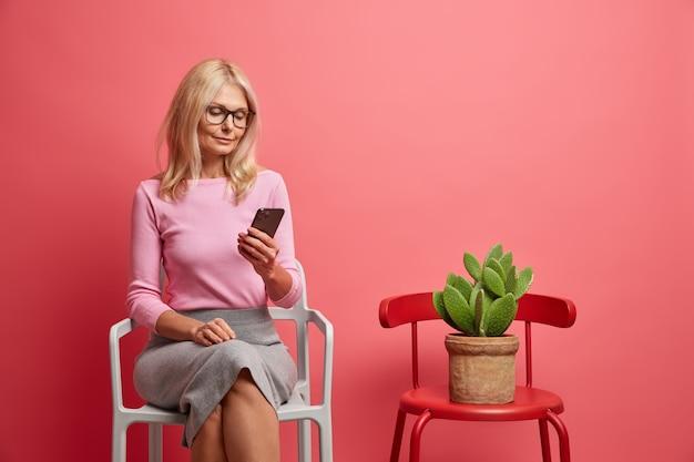 スマートフォンに集中してオンラインでニュースを読む女性は、ピンクに隔離された鍋にサボテンを入れた椅子の近くできちんとした服のポーズをとっている
