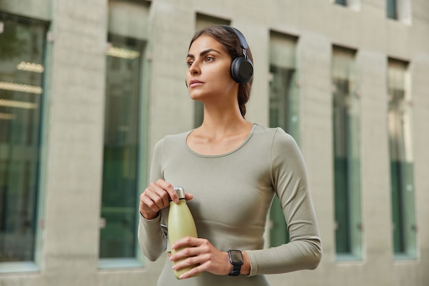 Woman concentrated into distance holds bottle of fresh water listens music via wireless headphonestakes break after sport training walks outdoor in city center