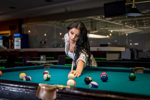 술집에서 당구 게임에 집중하는 여자