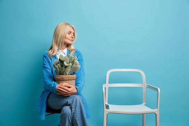 椅子に集中している女性は、鉢植えのサボテンを持ち、青に隔離されたファッショナブルな服を着て孤独を感じている