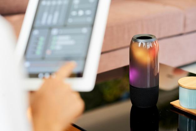 タブレットコンピューターのスマートホームアプリケーションにスピーカーを接続して、アプリを介して音楽を選択し、音量を制御する女性