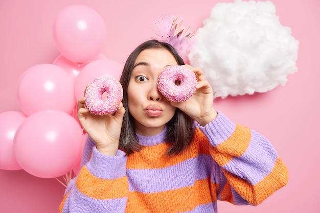 Женщина против глаз с вкусными пончиками держит губы сложенными, одетая в повседневный джемпер, празднует день рождения, наслаждается праздником, изолирована на розовом