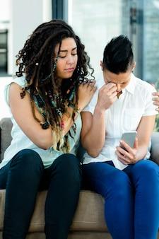 Женщина утешает своего партнера после прочтения сообщения в гостиной