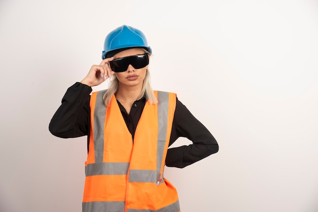 ゴーグルとヘルメットでポーズをとる女性建設業者。高品質の写真