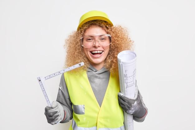 女性の建設エンジニアは建築プロジェクトを保持し、青写真を描き終えるのに幸せな巻尺は保護ヘルメットの制服を着ています