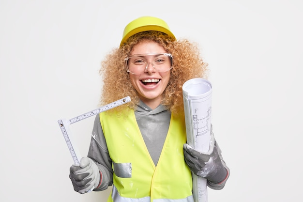 Woman construction engineer holds architectural project and tape measure happy to finish drawing blueprint wears protective helmet uniform