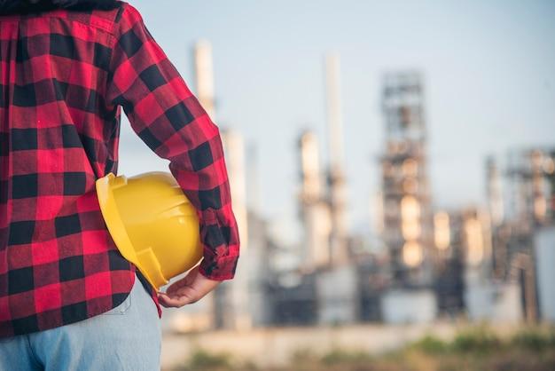 女性の建設エンジニアは、建設現場の産業労働者で安全白いヘルメットを着用します