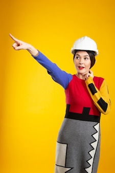 Woman in construction helmet points with finger
