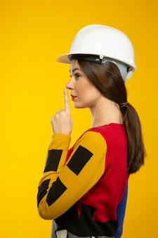 Woman in construction helmet shows to be silent