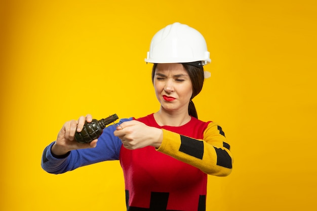 Woman in construction helmet with hand grenade replica