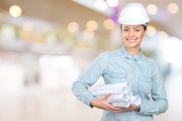 Woman construction worker or architect in a hardhat holding papers