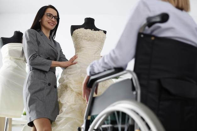 女性コンサルタントは、車椅子の女性にマネキンのウェディングドレスを実演します。