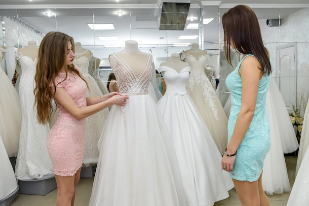 ブライダルガウンを選ぶ際に花嫁を助ける女性コンサルタント