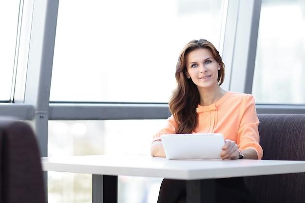 オフィスの職場でデジタルタブレットを使用している女性コンサルタント。コピースペース付きの写真。