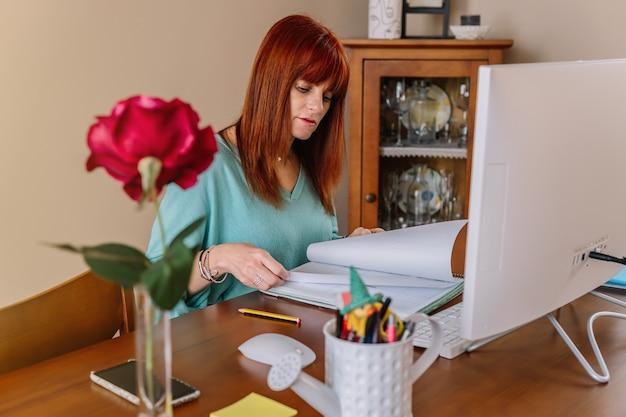 自宅のコンピューターの前で在宅勤務中にノートブックを参照している女性