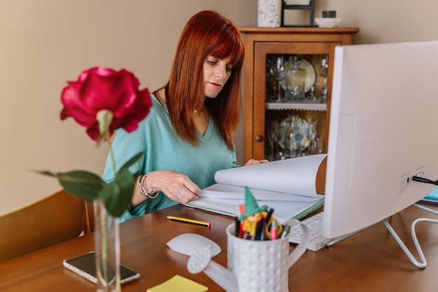 Woman consulting a notebook while teleworking in front of a computer at home