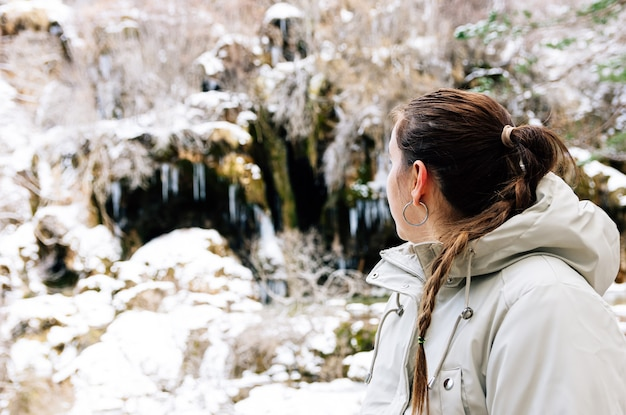Woman contemplating the birth of the cuervo river in cuenca, spain. snowy landscape in winter.