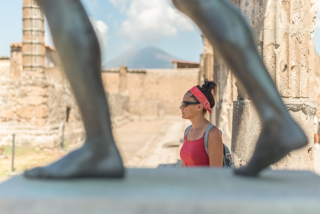 Woman contemplating the site of pompeii, in italy, with the vesuvius volcano in the background.
