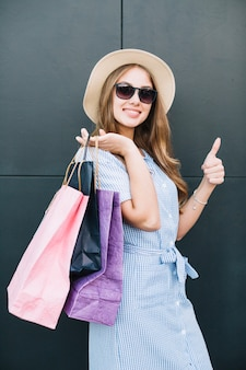 Woman content with purchases posing at camera