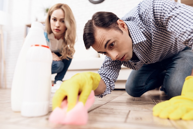 Woman control man cleaning floor in apartment.