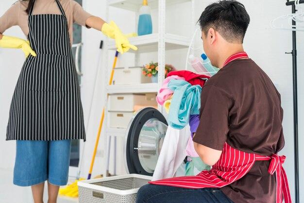 Женщина контролирует мужчину, чтобы стирать одежду в прачечной