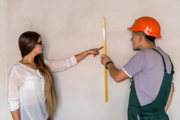 Женщина контролирует, как мужчина измеряет стену с помощью инструмента уровня