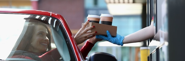Woman in convertible car picks up tea and coffee