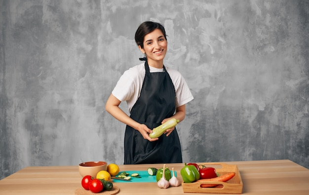 Woman cook black apron slicing vegetables cutting board kitchen cooking food.