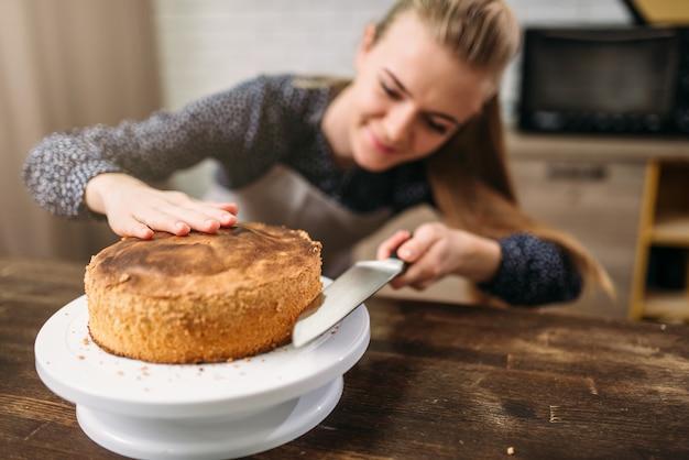Женщина-повар разрезал ножом свежеиспеченный торт.