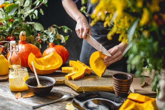 女性料理人は、オレンジ色のカボチャをナイフでスライスして焼きます