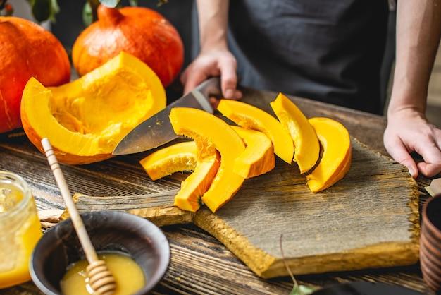 Женщина-повар режет ножом апельсиновую тыкву на дольки для запекания