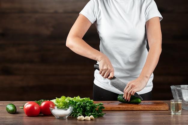 Повар женщины режет овощи для приготовления салата на древесине.