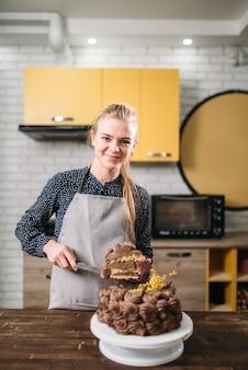 Женщина-повар держит на лезвии кусок шоколадного торта