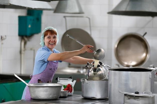 工業用厨房で料理をする女性が大きなスクープと笑顔でやかんに飲み物を注ぐ