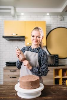 Женщина-повар в фартуке держит кулинарный шприц против шоколадного торта.