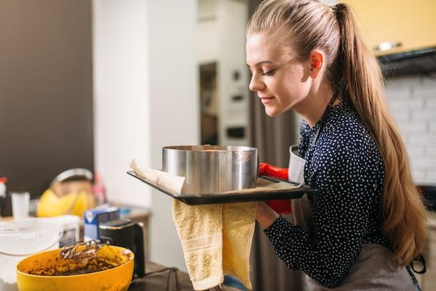 Повар женщины в фартуке держит горячую сковороду со свежим пирогом.