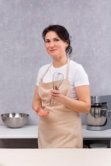 女性は台所のエプロンで泡立て器を手に持って料理をします。垂直フレーム。