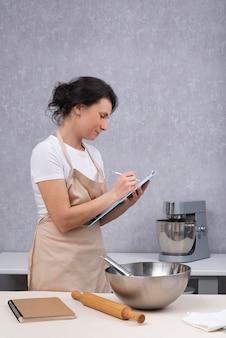 キッチンの女性料理人が新しい料理のレシピを書き留めています。
