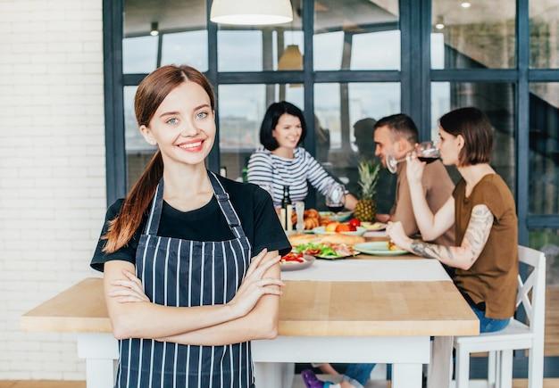 アパートのキッチンで人々とごちそうの背景に女性料理