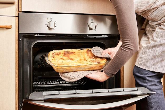Женщина-повар достает свежеиспеченную лазанью из горячей духовки