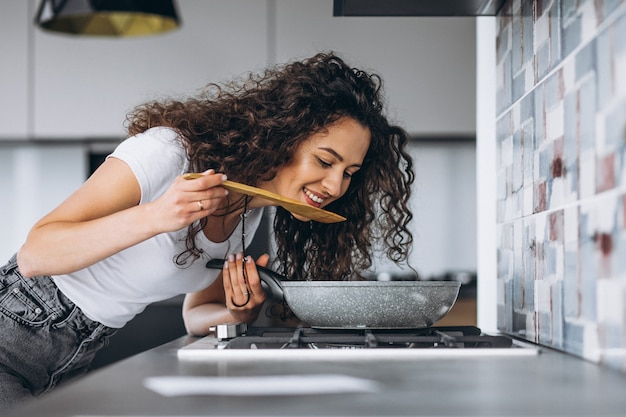 Женщина-повар готовит макароны на кухне
