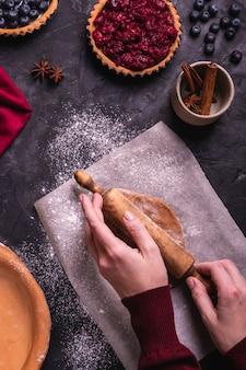 Женщина готовит рождественский пирог с ягодами
