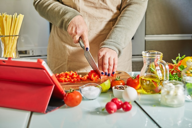 オンライン仮想マスタークラスのチュートリアルに従って料理をしている女性、そして健康的な食事を調理しながらタッチスクリーンタブレットを使用してデジタルレシピを見て