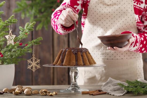 木製のキッチンでクリスマスケーキを調理する女性