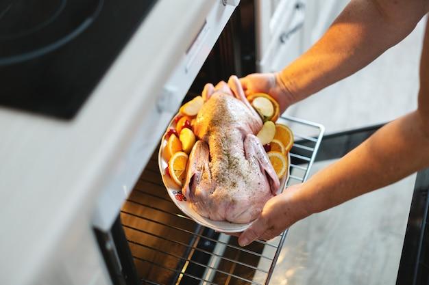 오븐에 야채와 함께 원시 오리를 넣어 크리스마스 오리를 요리하는 여자.
