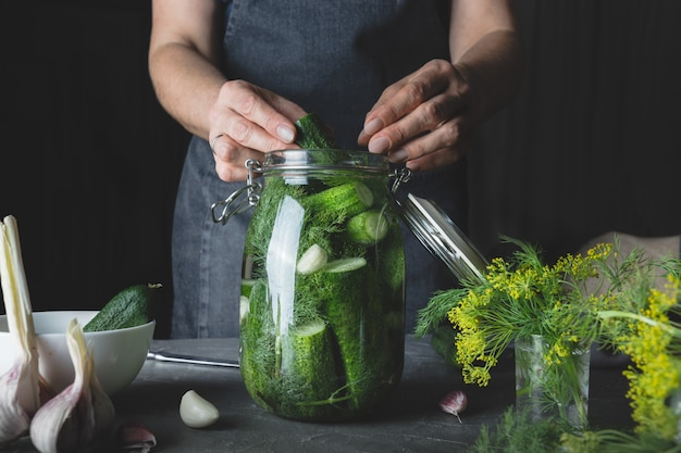 Woman cooking cucumbers with garlic and dill. rustic dark style. close up.