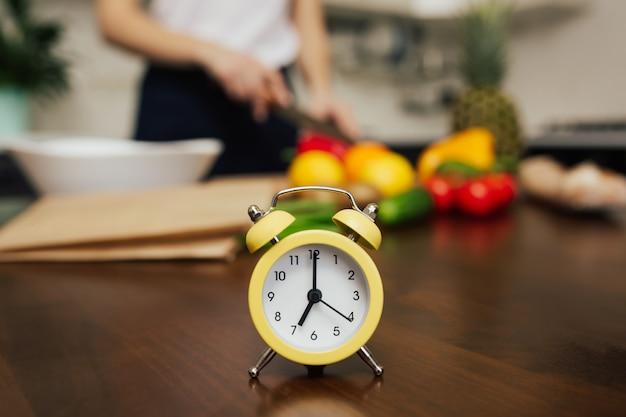 台所で夕食を作っている女性テーブルの上の小さな黄色い時計