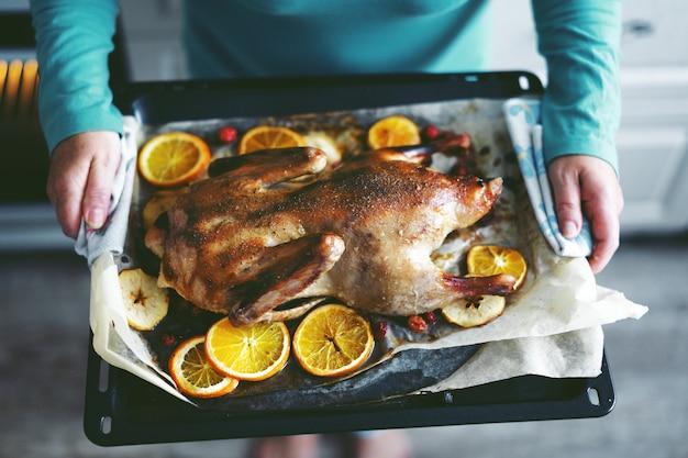 Женщина готовит утку с овощами и кладет ее из духовки.