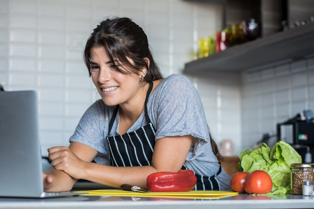 Woman cooking and following recipe on laptop pc