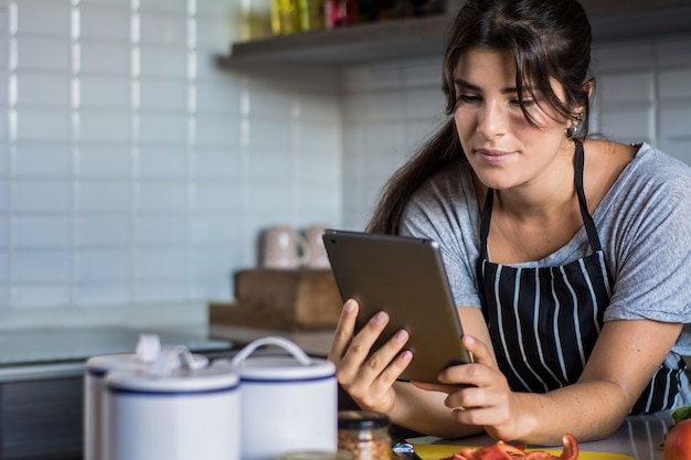 Woman cooking and following recipe on tablet pc